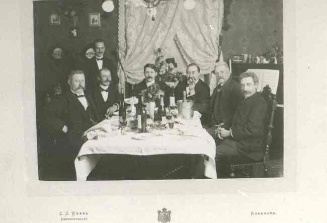 Groepsfoto van de heer J. Janssen en andere heren aan feestelijk gedekte tafel