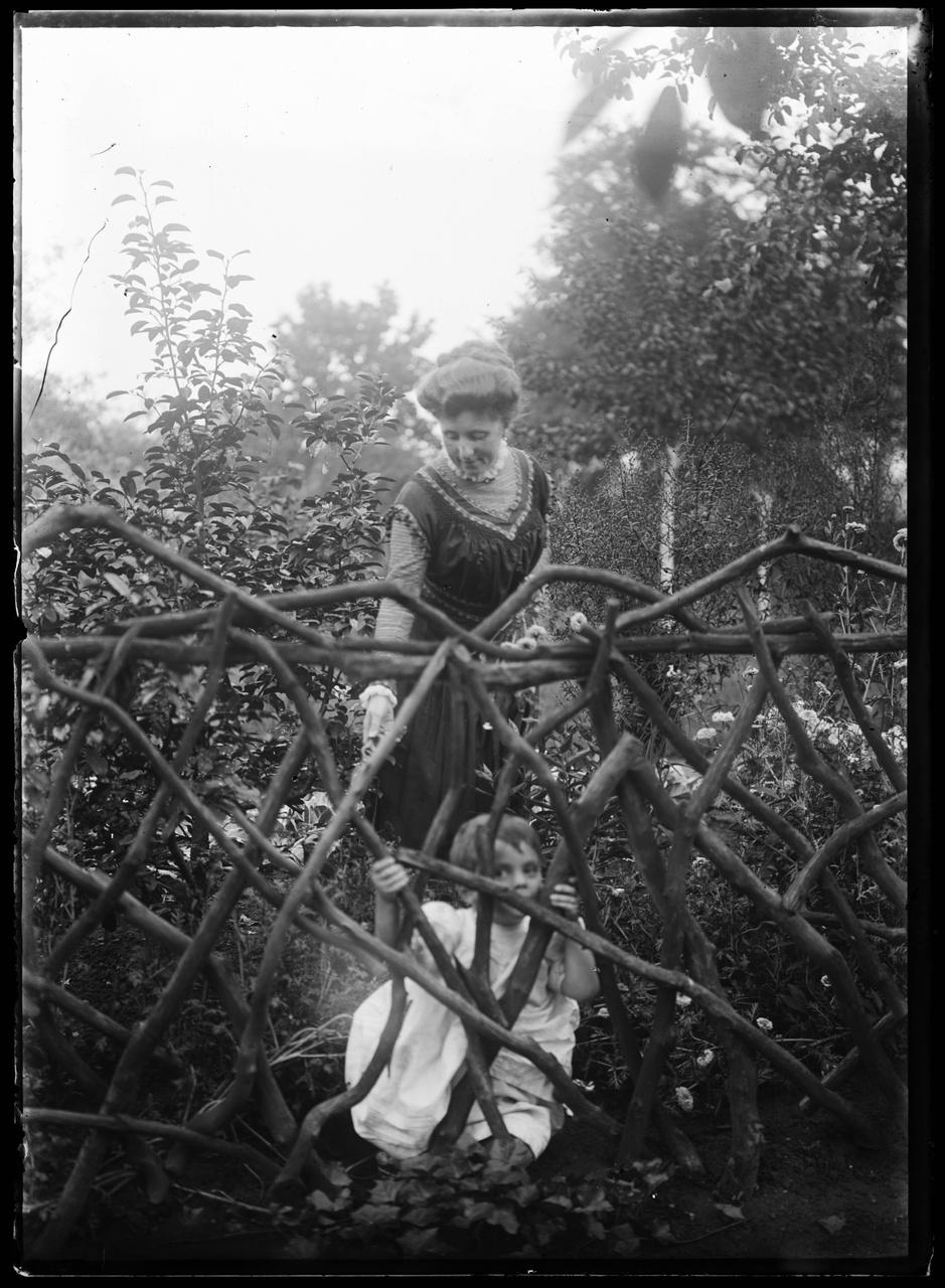 Glasnegatief van foto van vrouw en kind in tuin