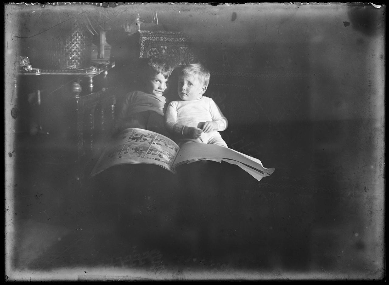 Glasnegatief van familiefoto, waarop twee kinderen met een stripboek