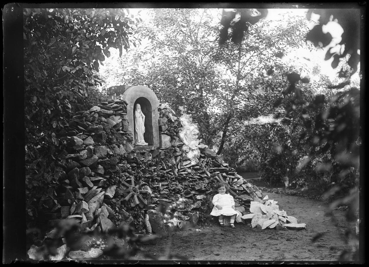 Glasnegatief van foto van kind in tuin met Lourdesgrot