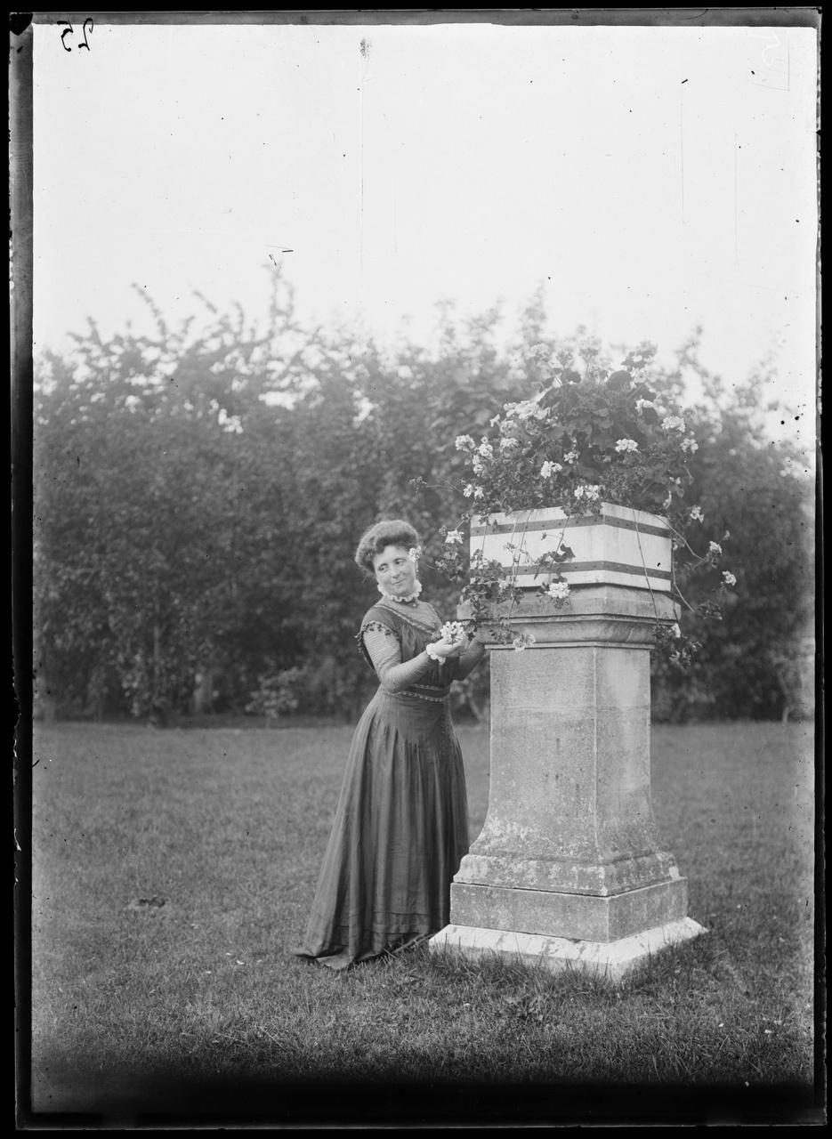 Glasnegatief van een foto van vrouw in tuin bij bloemenzuil