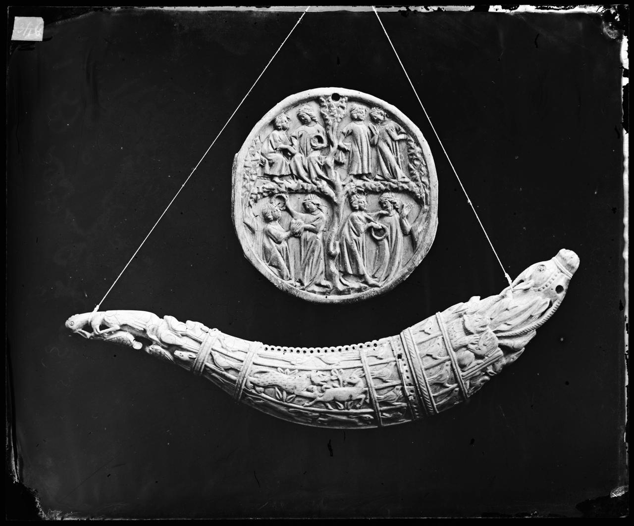 Glasnegatief van foto van producten uit de Cuypers' Kunstwerkplaatsen: Een kruithoorn en een medaillon