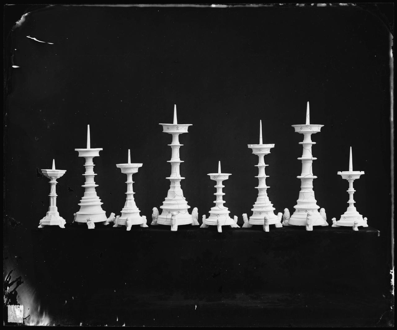 Glasnegatief van foto van producten uit de Cuypers' Kunstwerkplaatsen: Acht verschillende kandelaars